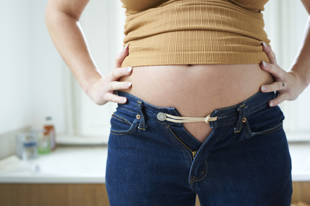 pregnant woman bursting out of jeans